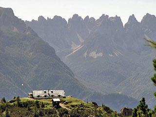 Il Rif. Ciaréido si staglia sullo sfondo degli Spalti di Tóro; lungo la salita a Forc. San Lorenzo